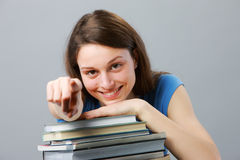 Girl Student. Beautiful girl student with stack of books pointing Stock Image