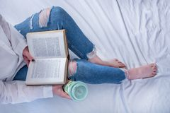 Girl student in blue jeans on leg and bare feet lying in cozy bed and reading book and holding retro coffee cup stock photo