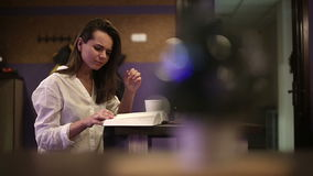 Girl student in a cafe reading a book stock footage