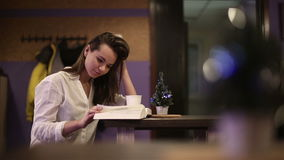 Girl student in a cafe reading a book. HD shot with slider stock footage