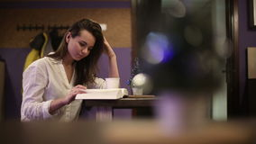 Girl student in a cafe reading a book. HD shot with slider stock video