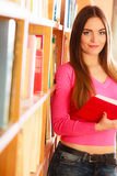 Girl student in college library. Education literature concept. Cheerful female student fashion girl long hair in college library choosing books. Indoor Royalty Free Stock Image