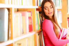 Girl student in college library. Education literature concept. Cheerful female student fashion girl long hair in college library choosing books. Indoor Royalty Free Stock Photos