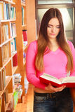 Girl student in college library. Education school concept. Attractive female student fashionable girl in college library looking for books. Indoor Stock Photography
