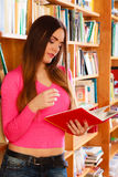 Girl student in college library. Education school concept. Attractive female student fashionable girl in college library looking for books. Indoor Royalty Free Stock Images