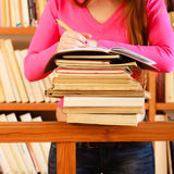 Girl student in college library. Education school concept. Intelligent female student fashion long hair girl in college library with stack books making research Stock Photography