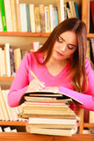 Girl student in college library. Education school concept. Intelligent female student fashion long hair girl in college library with stack books making research Stock Images