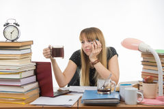Girl student doing night sadly looks another cup of coffee Royalty Free Stock Images