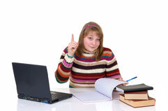 Girl student doing schoolwork. Teenage student girl doing schoolwork with laptop and books at desk, white background, reflective surface, studio shot Royalty Free Stock Photography