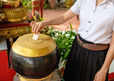 Girl student donate money for temple. Young thai girl student in uniform donate money for buddhism temple in Thailand Royalty Free Stock Photography
