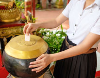 Girl student donate money for temple. Young thai girl student in uniform donate money for buddhism temple in Thailand Royalty Free Stock Photo