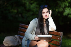 Girl student electronic tablet sitting on a bench Stock Image