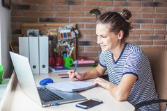 Girl student freelancer working with laptop at home by the window, education and remote work, programmer, online business royalty free stock photography