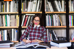 Girl student with glasses reading books in the library stock images