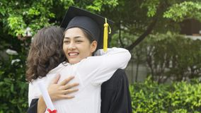 Girl student with the Graduation gowns and hat hug the parent in. The girl student with the Graduation gowns and hat hug the parent in congratulation ceremony Stock Images