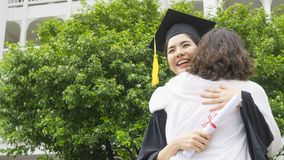 Girl student with the Graduation gowns and hat hug the parent in. The girl student with the Graduation gowns and hat hug the parent in congratulation ceremony Stock Image