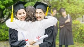 Girl student with the Graduation gowns and hat hug the parent in. The girl student with the Graduation gowns and hat hug the parent in congratulation ceremony Royalty Free Stock Image