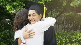 Girl student with the Graduation gowns and hat hug the parent in. The girl student with the Graduation gowns and hat hug the parent in congratulation ceremony stock photo