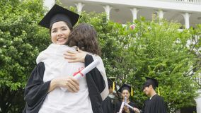 Girl student with the Graduation gowns and hat hug the parent in. The girl student with the Graduation gowns and hat hug the parent in congratulation ceremony Royalty Free Stock Photos