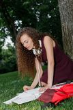 Girl student holding book and sitting under tree Stock Images
