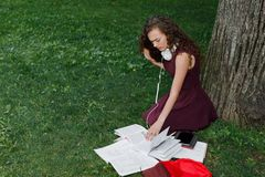 Girl student holding book and sitting under tree Stock Photo
