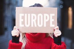Girl student holding a sign with the inscription `Europe`. Hitchhiking around Europe. royalty free stock photography