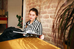 Girl student at home at table studying reading book Royalty Free Stock Photos