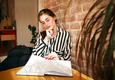 Girl student at home at table studying reading book Royalty Free Stock Image