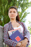 Girl student looks into the distance and keeps her books Stock Photography