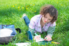 Girl student in park writes  writing book Royalty Free Stock Image