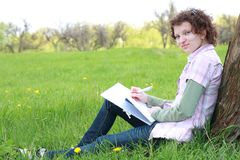Girl student in park writes  writing book Royalty Free Stock Photo