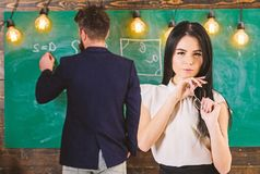 Girl student play with eyeglasses while teacher writes on chalkboard. Lady on dreamy face not pay attention to teacher royalty free stock photography