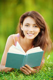 Girl-student read a textbook. Pretty girl-student is on the lawn and read a textbook Stock Photography