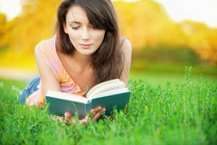 Girl-student read a textbook. Pretty girl-student is on the lawn and read a textbook Royalty Free Stock Photo