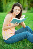 Girl-student read a textbook. Beautiful girl student sitting on the lawn and read a textbook Royalty Free Stock Images