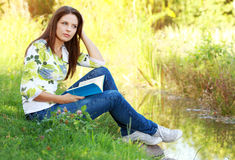 Girl student reading book in autumn park. Stock Photography