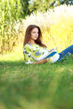 Girl student reading book in autumn park. Stock Image