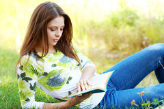 Girl student reading book in autumn park. Royalty Free Stock Images