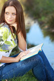 Girl student reading book in autumn park. Stock Photo
