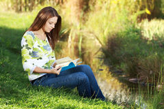 Girl student reading book in autumn park. Stock Images