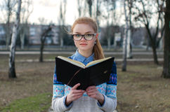 Girl student reading book. Redhead student girl standing , holding and reading a book in park Stock Images