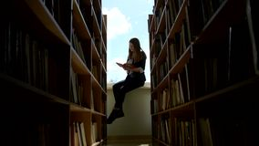 Girl student reading a book on a window sill at. Girl -  student reading a book on a window sill at the library. around the book. camera moves right stock footage