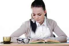 Girl student reads a book at the table Royalty Free Stock Photography