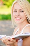 Girl-student reads textbook. Smiling girl-student reads textbook against summer nature Royalty Free Stock Photos
