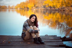 Girl student rests on the pier. Beautiful scenery, autumn and the river. Creative colors Stock Images