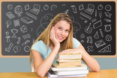 Girl student seated with books in front of black board with drawings Royalty Free Stock Images