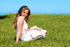 Girl-student sit on lawn and reads textbook. Happy Girl-student sit on lawn and reads textbook Royalty Free Stock Photo