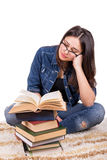 Girl student sitting with a pile of books Stock Photos