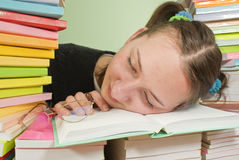 Girl student sleeping on stack of books Royalty Free Stock Images
