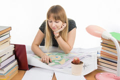Girl student with a smile looks at a drawing master plan at a table cluttered with books Royalty Free Stock Photography